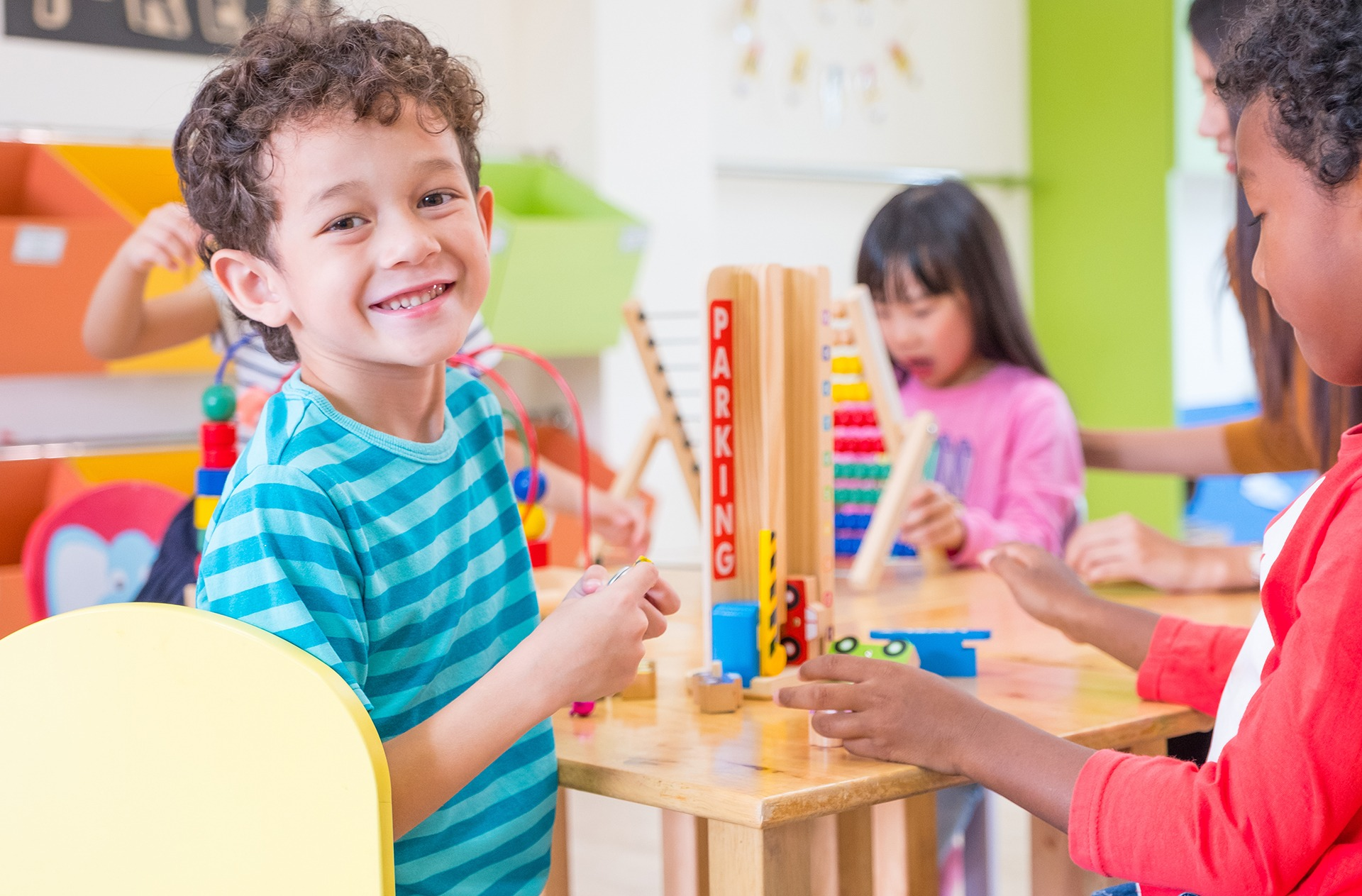 Kindergarten Students Smile When Playing Toy In Playroom At Pres