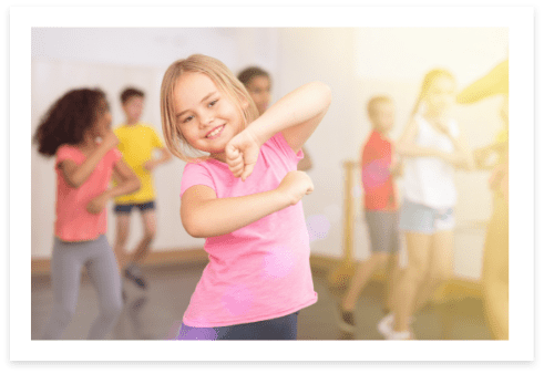 little girl dressed in pink, smiling and dancing