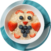 bowl of porridge and fruit made into a smiling face