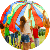 group of children playing with a multicoloured parachute