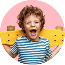 smiling little boy holding a yellow skateboard