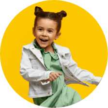 little girl smiling dancing on a yellow background