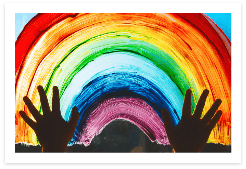 painting of a rainbow on a window, with hands